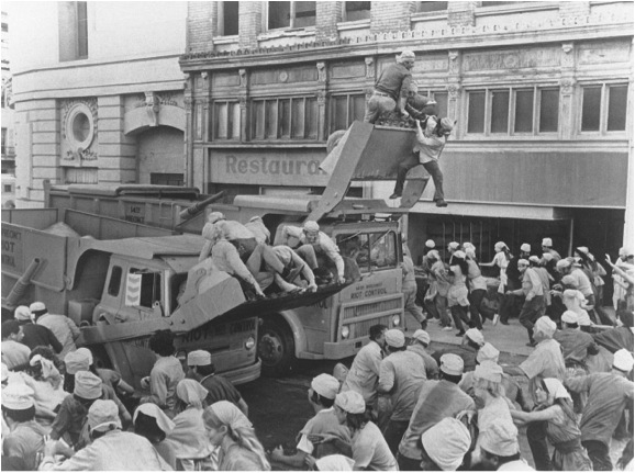 Riot Control trucks push their way through the crowds after an uprising over food shortages.